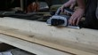 Work carpenter in the workshop. Treatment of wooden planks electric tool
