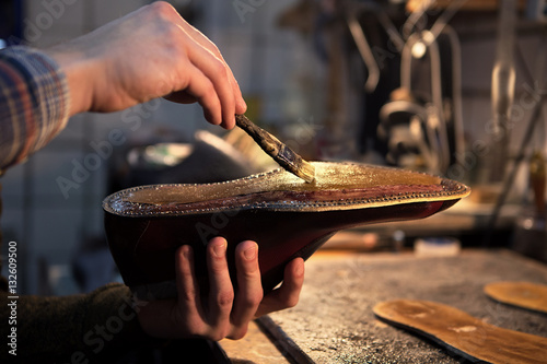 Shoemaker makes shoes for men. He smears special liquid  with a brush.