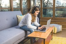 Teenage Girl On Laptop With Headphone In The Conservatory