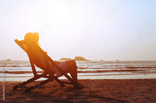 Photo happy summer beach holidays, woman relaxing in deckchair at sunset