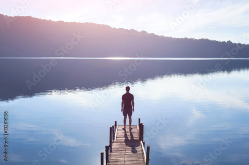 Fototapeta dreamer, silhouette of man standing on the lake wooden pier at sunset, human str