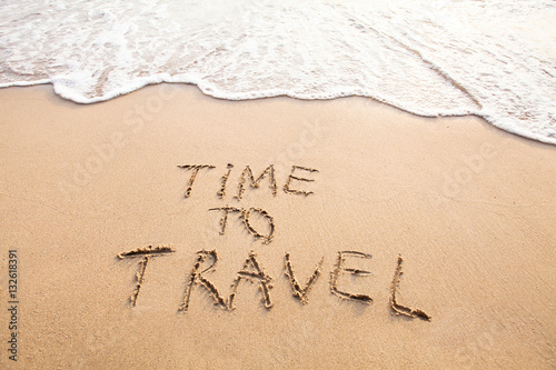Fototapeta time to travel, concept text drawn on sand of beach