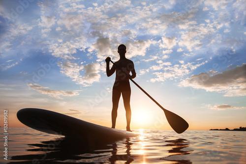 Plakat wiosło stojący, sylwetka człowieka na plaży o zachodzie słońca