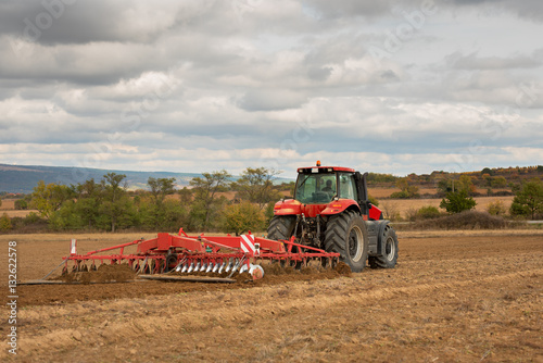 Vászonkép  Farmer in tractor preparing land with seedbed cultivator