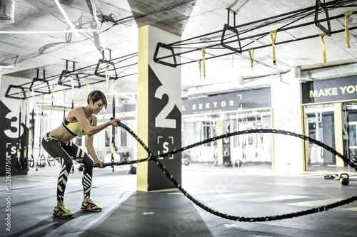 Foto op Plexiglas Fitness Girl does exercise with fitness rope in gym