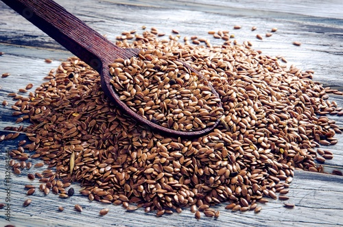 Linseed with wooden spoon on a wooden board.
