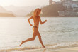 Back view of fit slim girl running barefoot on seashore wearing bikini. Young woman doing cardio exercise beach lit in sunshine and city mountains in background.