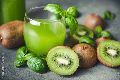 Kiwi and basil refreshing juice on gray rock surface.