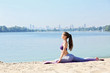 Attractive young woman doing yoga by the river