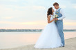 Beautiful wedding couple near river at sunset