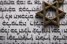Religion And Judaism Concept With Closeup On A Text In Hebrew From The Holy Torah And Macro On The Star Of David