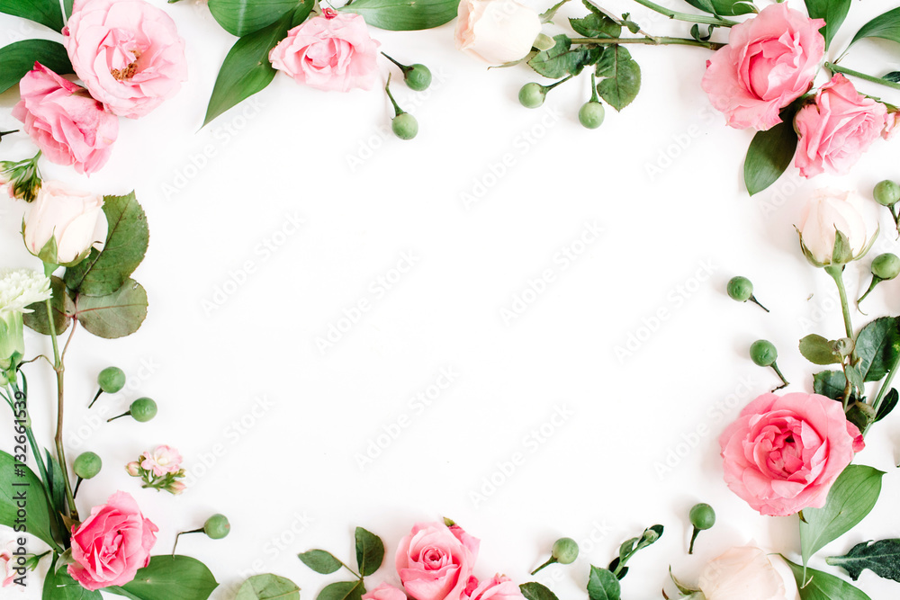 Fototapeta Round frame made of pink and beige roses, green leaves, branches on white background. Flat lay, top view. Valentine's background