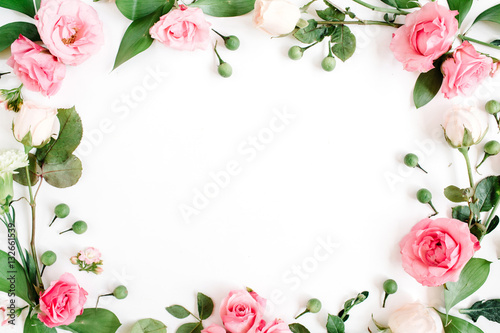 Obraz Round frame made of pink and beige roses, green leaves, branches on white background. Flat lay, top view. Valentine's background - fototapety do salonu