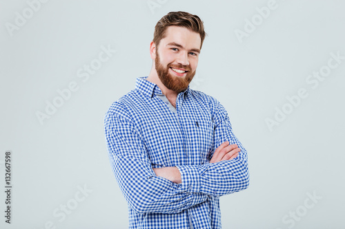 Fotografie, Obraz  Happy handsome young man standing with arms crossed