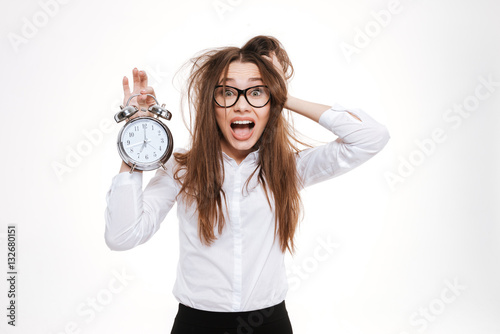 Fotografía  Scared young business woman holding alarm clock a