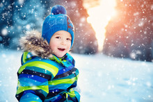 Boy In Knitted Hat, Gloves And Scarf Outdoors At Snowfall