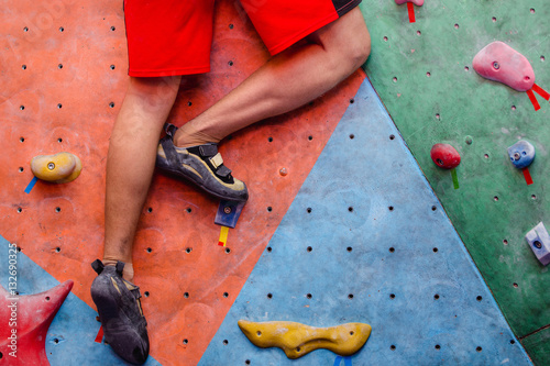 Photo  Man climbing artificial boulders in gym, close-up view of legs with special shoe