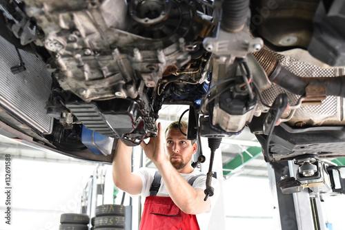 Zdjęcie XXL Mechanik samochodowy naprawy uszkodzony pojazd na podnośniku w warsztacie