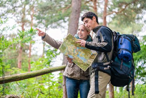 Junges Paar, Frau und Mann, beim Wandern suchen den richtigen Weg mit Wanderkart Poster