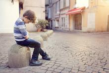 Lonely Child Sitting On A Street Corner