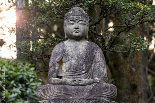 Photo  Old stone Buddha  - statue at a park