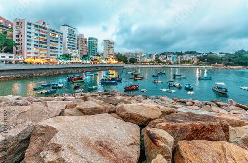 Zdjęcie XXL Skalisty denny brzeg Stanley zatoka na Hong Kong wyspie w Hong Kong. Piękny sceniczny krajobraz z wodą, górami, skałami, budynkami, łodziami rybackimi i chmurnym niebem