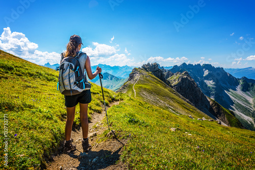 Obraz Hiker in boots and backpack holds walking stick - fototapety do salonu