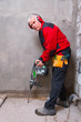 Builder worker with jackhammer hammer equipment at the construct