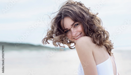 Happy woman on the beach. Portrait of the beautiful girl close-up, the wind fluttering hair. Spring portrait on the beach. Young pretty girl. Young smiling woman outdoors portrait. Close portrait.