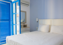 Empty Hotel Room In Traditional Mediterranean Style With Blue Bl