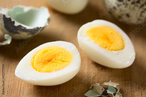 Hard boiled quail egg halves with egg shells on wooden board, photographed with natural light (Selective Focus, Focus in the middle of the left egg half)