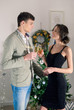 Beautiful young couple is holding glasses of champagne and smili