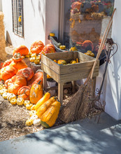 Display Of Pumpkins Against Farm House Wall With Two Brooms And