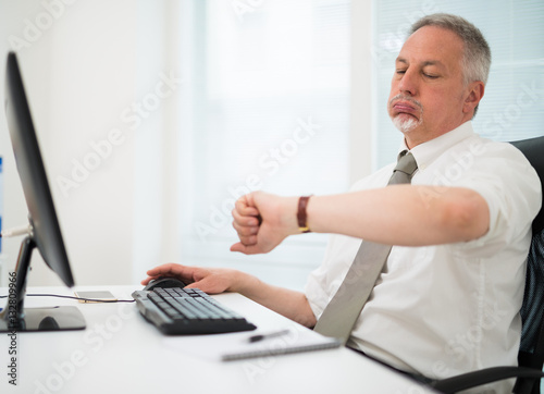 Photo Impatient businessman watching his wrist watch in the office