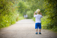 Top View On Cite Little Toddler Boy In Straw Hat Walking On The Countryside Road On Sunset. Lifestyle Concept