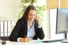 Businesswoman Calling On Phone And Taking Notes
