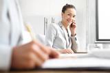 Doradca kredytowy. Bizneswoman rozmawia przez telefon siedząc przy biurku.