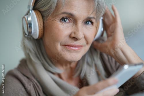 Foto  Ältere Frau zu Hause, die Musik mit Smartphone hört