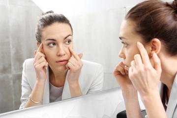Odbicie w lustrze. Kobieta przegląda się w lustrze dostrzegając pierwsze zmarszczki