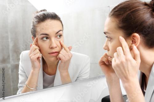 Odbicie w lustrze. Kobieta przegląda się w lustrze dostrzegając pierwsze zmarszczki  - fototapety na wymiar
