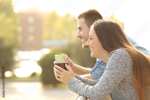Leinwand Poster Happy couple enjoying breakfast in a balcony