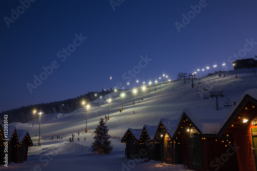 Photographie  winter market village in Levi, Finland in the evenig on ski cable way background