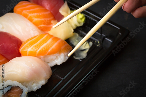 Poster Sushi bar Hand using chopsticks pick. Sushi and Sashimi rolls on a black stone slatter. Fresh made Sushi set with salmon, prawns, wasabi and ginger. Traditional Japanese cuisine..
