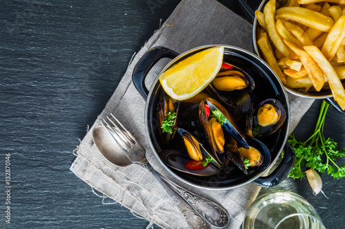 Poster Seafoods Mussels in pan on rustic background