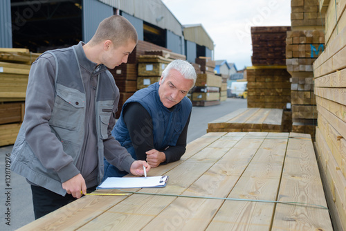 Photo Men leaning on stack of wood studying clipboard