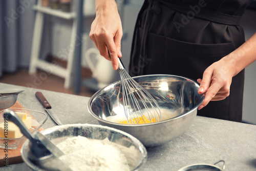 Poster Cuisine Young woman cooking in kitchen, closeup