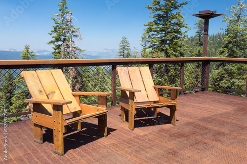 Fotografie, Obraz  Two wood chairs on outdoor sunny deck with mountains in the background
