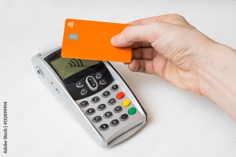 Fototapeta Customer is paying using contactless credit card and payment terminal.