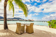 Two chairs and table on a sand beach with a view on the lagoon a