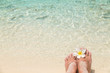 canvas print picture Bare female feet with frangipani flower in the water of the sea